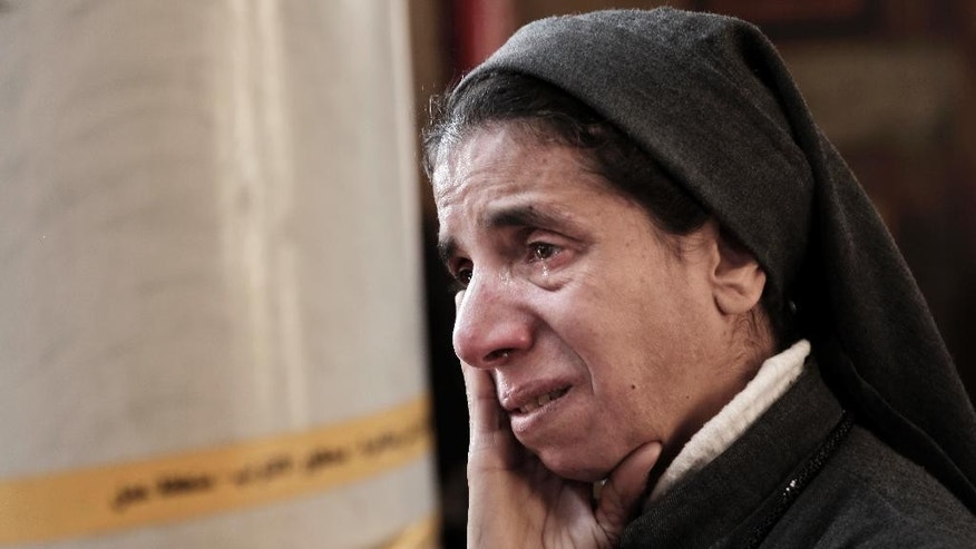 "FILE -- In this Dec. 11, 2016 file photo, an Egyptian Coptic nun weeps as she looks at damage inside the St. Mark Cathedral in central Cairo, following a bombing. A 20-minute video from an Islamic State affiliate in Egypt, which emerged Monday, Feb. 20, 2017, showed the suicide bomber who attacked the church and vowed more attacks on the country's Christian minority. The video said Christians are the extremist group's ""favorite prey."" (AP Photo/Nariman El-Mofty, File)"