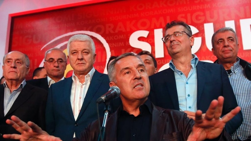 In this Monday, Oct. 17, 2016 file photo, former Montenegro's Prime Minister and long-ruling Democratic Party of Socialists leader Milo Djukanovic, center, speaks in his headquarter, in Podgorica, Montenegro. Montenegro's special prosecutor  Milivoje Katnic, has accused Russia and its secret service operatives of plotting a coup attempt that included plans to kill the small Balkan country's former prime minister, Milo Djukanovic, following an investigation.  (AP Photo/Darko Vojinovic, File)