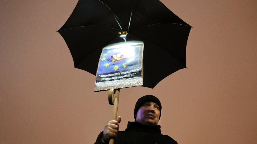 "A protesters holds an umbrella with a banner that reads ""We want a democratic Romania, not an oligarchic Romania"" outside the government headquarters in the rain in Bucharest, Romania, Sunday, Feb. 19, 2017. Braving the bad weather thousands gathered for the twentieth consecutive day to demand the government's resignation after it passed a decree, since withdrawn, that would have softened the corruption fight that has targeted top officials. (AP Photo/Vadim Ghirda)"