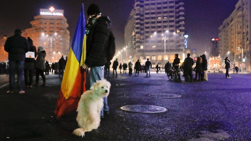 FILE - In this Thursday, Feb. 2, 2017, file picture a man wearing a gas mask holds a Romanian flag as a his dog sits next to him at the end of a protest joined by tens of thousands against a government decree that dilutes what qualifies as corruption, in Bucharest, Romania. In recent weeks, hundreds of thousands of Romanians have used humor, wit and hip symbols in anti-corruption protests sparked by a government decree that would have diluted the anti-graft drive.(AP Photo/Vadim Ghirda, FILE)