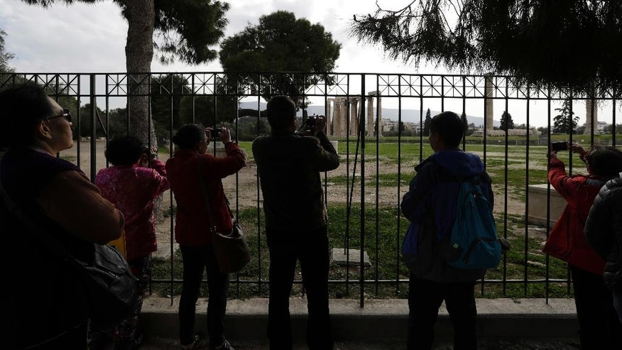 Chinese tourists take photographs behind a fence of the ancient Temple of Zeus as state guards called a 24-hour strike over a pay and contract dispute with the government in Athens, Monday, Feb. 20, 2017. Monday's protest was not directly related to Greece's bailout measures, but the country's left-wing government is under renewed international pressure to limit spending and agree with lenders on new austerity measures and reforms. (AP Photo/Thanassis Stavrakis)