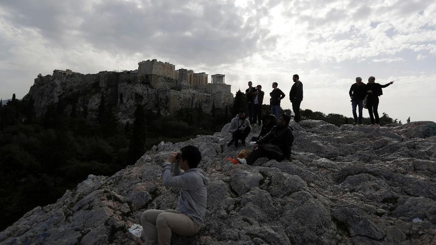 Tourists stand on a hill under ancient Acropolis hill during a 24-hour strike by archaeological guards demanding unpaid wages and the recruitment of additional employees in Athens, Monday, Feb. 20, 2017. Greece has been struggling for months to conclude negotiations with its creditors on spending cuts and reforms demanded by European creditors and the International Monetary Fund as part of its third bailout program. (AP Photo/Thanassis Stavrakis)