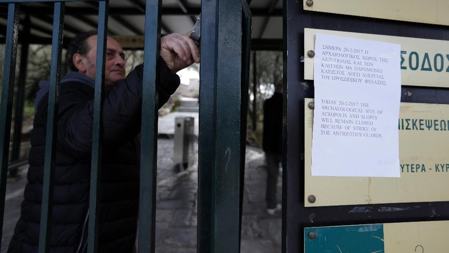 A worker of Culture Ministry closes the entrance of the ancient Acropolis hill during a 24-hour by archaeological guards, demanding unpaid wages and the recruitment of additional employees, in Athens, Monday, Feb. 20, 2017. Greece has been struggling for months to conclude negotiations with its creditors on spending cuts and reforms demanded by European creditors and the International Monetary Fund as part of its third bailout program. (AP Photo/Thanassis Stavrakis)