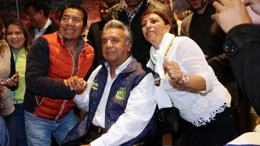 Lenin Moreno, presidential candidate for the ruling party Alliance PAIS, center, poses for a photo with supporters after a news conference in Quito, Ecuador, Monday, Feb. 20, 2017. The hand-picked candidate of President Rafael Correa, Moreno held an easy lead Monday in Ecuador's presidential election, though authorities said it might be a few more days before they determine if Moreno won enough votes to avoid a runoff against his nearest rival. (AP Photo/Dolores Ochoa)