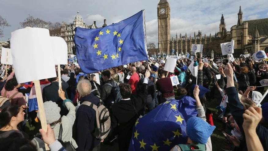 Demonstrators wave flags in Parliament Square before a group of EU citizens of several nationalities, and including nurses, social workers and teaching assistants,  lobby Members of Parliament  over their right to remain in the UK, in London, Monday Feb. 20, 2017. The House of Lords begins to debate the Government's Brexit bill on Monday. (AP Photo/Tim Ireland)