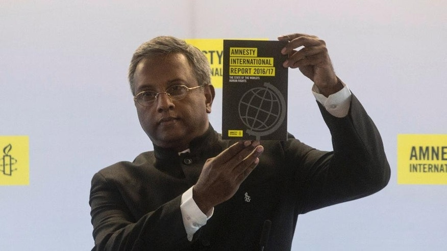 Secretary General of Amnesty International, Salil Shetty, shows the 2016/2017 Amnesty International report during a press conference, in Paris, Tuesday, Feb. 21, 2017. (AP Photo/Thibault Camus)