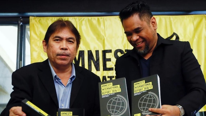 "Amnesty International, Philippines' Jose Noel Olano, left, and Wilnor Papa, hold copies of the 2016/17 Amnesty International report which they released at a news conference Wednesday, Feb. 22, 2017, in suburban Quezon city northeast of Manila, Philippines. Amnesty International says ""toxic"" fear-mongering by anti-establishment politicians, among them President Donald Trump and the leaders of Turkey, Hungary and the Philippines, is contributing to a global pushback against human rights. (AP Photo/Bullit Marquez)"