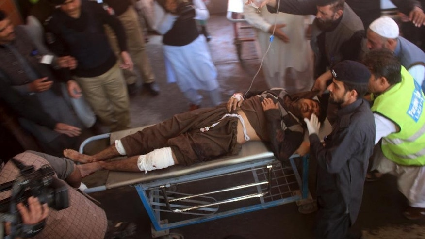 Pakistani volunteers rush an injured person to an emergency ward at a hospital in Peshawar, Pakistan, Tuesday, Feb. 21, 2017. Police say three suicide bombers have attacked a courthouse in northwestern Pakistan. Charsadda police chief says one of the bombers detonated his suicide vest at the court's main gate while police shot and killed the two other assailants. (AP Photo/Mohammad Sajjad)