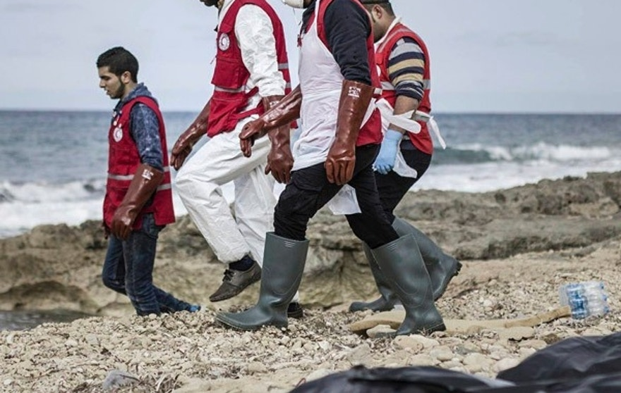 This Monday, Feb. 20, 2017 photo provided by The International Federation of Red Cross and Red Crescent Societies (IFRC), shows Libyan Red Crescent workers recovering bodies of people that washed ashore, near Zawiya, Libya. The Libyan Red Crescent says at least 74 bodies of African migrants have washed ashore in western Libya, the latest tragedy at sea along a perilous trafficking route to Europe. It says the bodies were found on Monday, and that more may yet surface. (Mohannad Karima/IFRC via AP)