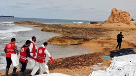 This Monday, Feb. 20, 2017 photo provided by The International Federation of Red Cross and Red Crescent Societies (IFRC), shows the bodies of people that washed ashore and were recovered by the Libyan Red Crescent, near Zawiya, Libya. The Libyan Red Crescent says at least 74 bodies of African migrants have washed ashore in western Libya, the latest tragedy at sea along a perilous trafficking route to Europe. It says the bodies were found on Monday, and that more may yet surface. (Mohannad Karima/IFRC via AP)