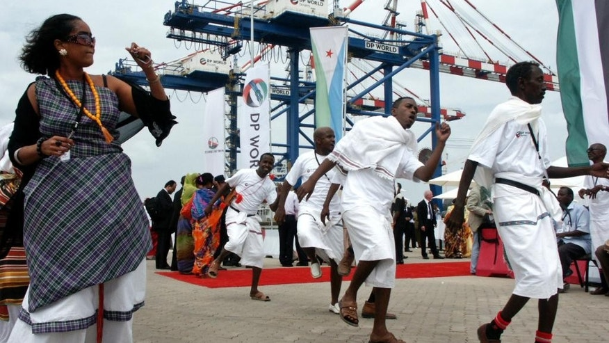 FILE -- In this Feb. 7, 2009 file photo, Djibouti men and women dance during the opening ceremony of Dubai-based port operator DP World's Doraleh container terminal in Djibouti port. Dubai's government media office said Tuesday, Feb. 21, 2017, that an arbitration tribunal has cleared port operator DP World of allegations of wrongdoing over its operation of an East African port. The government of Djibouti brought a legal challenge against Dubai's state-backed DP World in 2014 over its 50-year deal to operate the Doraleh Container Terminal, accusing it of bribing the head of Djibouti's port authority. (AP Photo/Adam Schreck, File)