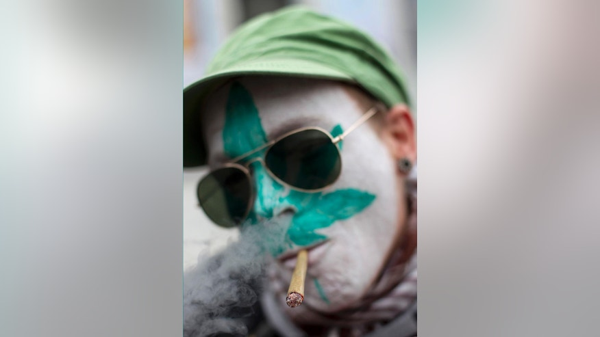 In this Friday April 20, 2012 file image a protestor from Belgium with a marijuana leaf painted on his face smokes a marijuana joint in Amsterdam during a protest against a government plan to stop foreigners from buying marijuana in the Netherlands. Dutch lawmakers have voted in favor of tolerating the cultivation of cannabis, in what would be a new expansion of the country's relaxed pot policy and bring to an end one of its paradoxes. (AP Photo/Peter Dejong)