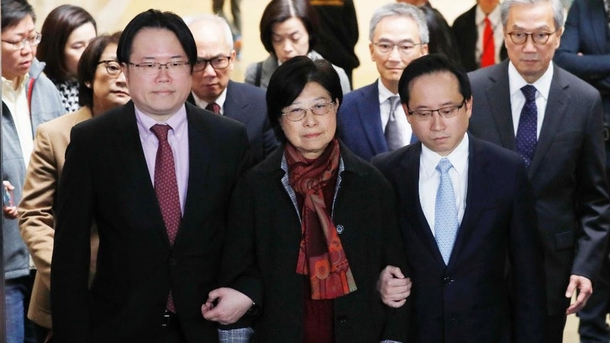 Selina Tsang, center, wife of former Hong Kong leader Donald Tsang, is accompanied by her two sons, Simon Tsang Hing-yin, left, and Thomas Tsang Hing-shun, to walk out of the High Court in Hong Kong, Wednesday, Feb. 22, 2017. The former leader of Hong Kong was sentenced Wednesday to 20 months in prison for misconduct after failing to disclose plans to rent a luxury apartment for his retirement from a businessman applying for a broadcasting license. (AP Photo/Kin Cheung)