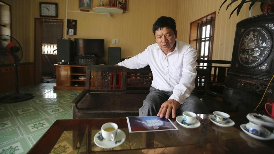 "Doan Van Thanh, the father of a Vietnamese woman arrested in the death of Kim Jong Nam in Malaysia, looks at an image of his daughter, during an interview at his home in Nghia Binh village in northern province of Nam Dinh, Vietnam, Tuesday, Feb. 21, 2017. The family of Doan Thi Huong arrested in the death of the half brother of North Korea's ruler, confirmed she is their relative, but believes she didn't knowingly participate in the killing. Thanh said he is the father of Huong, but cannot believe she would do such an ""Earth-shaking"" thing. (AP Photo/Duong Minh Hoang)"