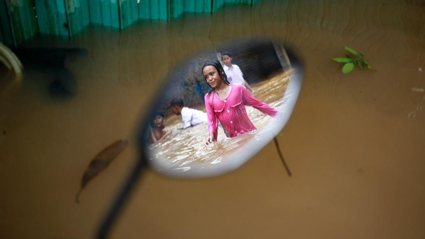 The reflection of a girl is seen on a mirror of a motorcycle left at a flooded neighborhood in Jakarta, Indonesia, Tuesday, Feb. 21, 2017. Torrential rains in the Indonesian capital have overwhelmed drains and flooded roads and thousands of homes. Floods and deadly landslides are a fact of life for Indonesians during the wet season, with other major cities suffering repeated flooding. (AP Photo/Dita Alangkara)