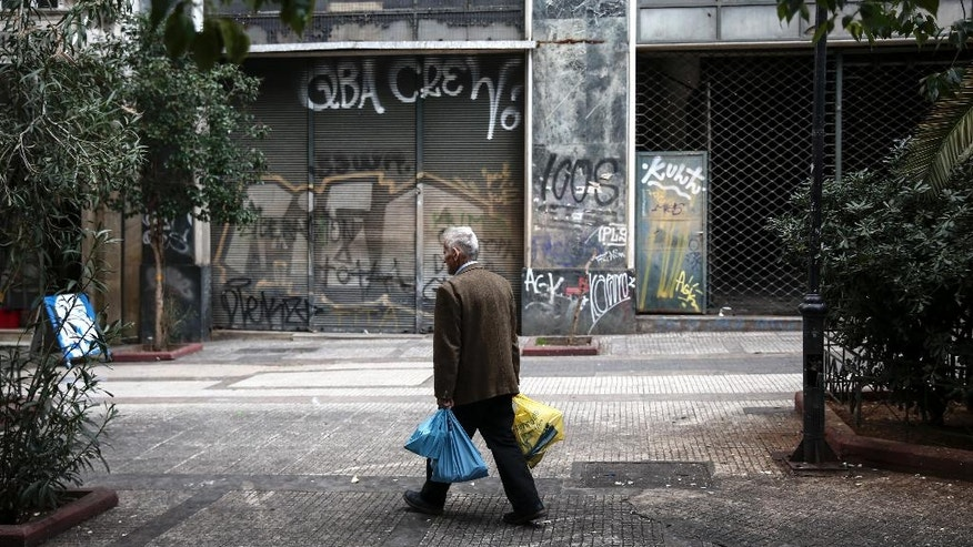 A man carries shopping bags as he walks on a pedestrian street of Athens, Tuesday, Feb. 21, 2017. Greece and its European creditors agreed Monday to resume talks on what economic reforms the country must make next in order to get the money it needs to avoid bankruptcy and a potential exit from the euro this summer. (AP Photo/Yorgos Karahalis)