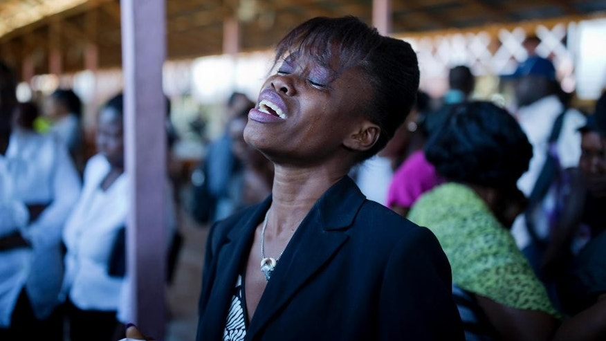"Ludji Belizaire cries in front of the coffin which contains the body of her brother Etzer Belizaire, during the mass burial of inmates who died at the country's largest prison in Port-au-Prince, Haiti. Tuesday Feb. 21, 2017. Ludjy Belizaire said she visited her incarcerated 25-year-old brother Etzer as often as she could over the last year, especially when he started complaining that he was weak with hunger and getting sick. He began shedding weight rapidly. ""He got skinnier and skinnier. After a while, he didn't even look like himself anymore,"" she said, adding that her brother was jailed for six years on illegal gun charges without ever going before a judge. ( AP Photo/Dieu Nalio Chery)"