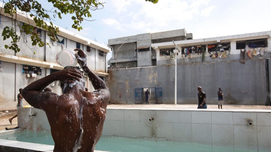 In this Feb. 13, 2017 photo, a prisoner bathes during recreation time inside the National Penitentiary in downtown Port-au-Prince, Haiti. Inmates, some waiting up to eight years to see a judge, try to keep their sanity by maintaining a daily routine. (AP Photo/Dieu Nalio Chery)