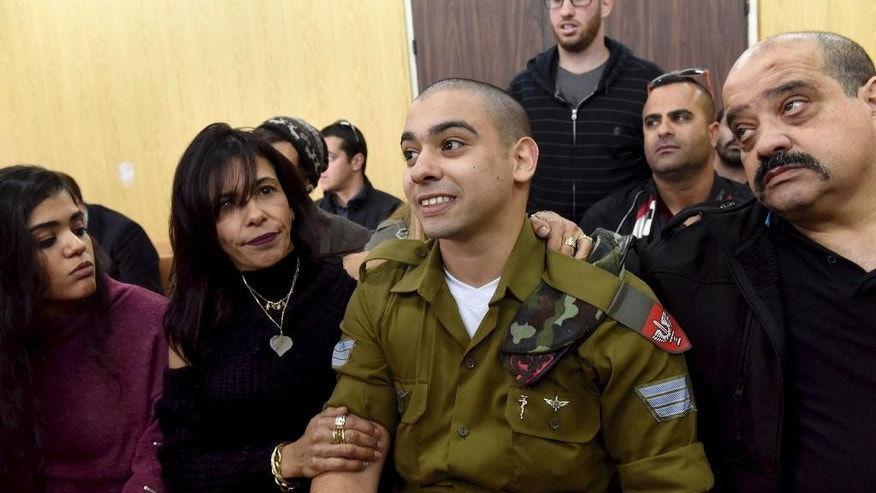 FILE -- In this January 24, 2017 file photo, Israeli soldier Sgt. Elor Azaria attends a sentencing hearing in the military court surrounded by his family, in Tel Aviv, Israel. The Israeli army said a military court on Tuesday, Feb, 21, 2017,  will sentence a soldier convicted of manslaughter for fatally shooting a wounded Palestinian assailant. Azaria faces a maximum sentence of 20 years, though analysts expect him to receive less than that. (Debbie Hill, Pool via AP, File)