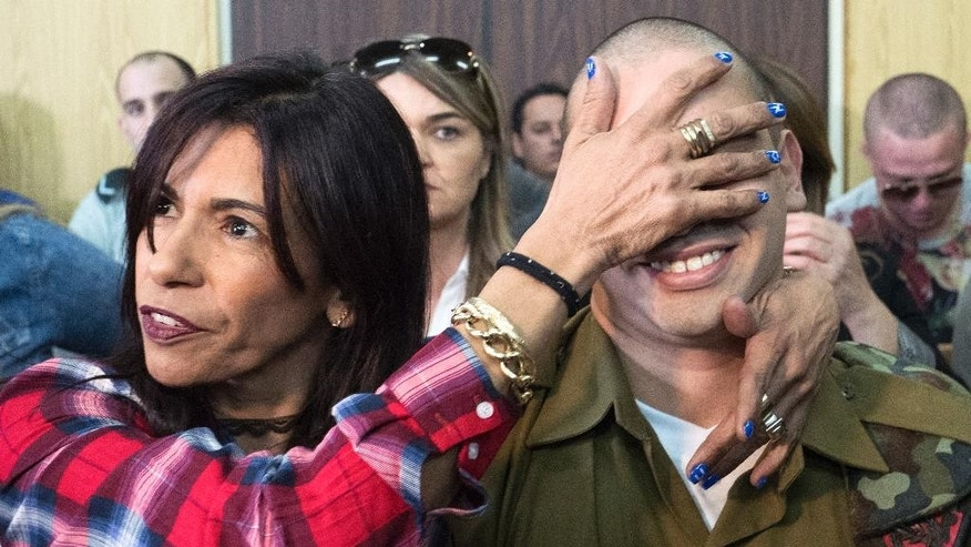 Israeli soldier Elor Azaria is embraced by his mother at the start of his sentencing hearing in the Israel military court, Tel Aviv, Israel, Tuesday, Feb. 21, 2017. The court sentenced Azaria to 18 months in prison for the fatal shooting of a wounded Palestinian assailant. Prosecutors had asked that Sgt. Elor Azaria be sentenced to 3-5 years in prison. (Jim Hollander, Pool, via AP)