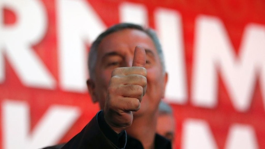 "FILE - This is a  Monday, Oct. 17, 2016 file photo, of former Montenegro's Prime Minister and long-ruling Democratic Party of Socialists leader Milo Djukanovic, as he the gives a thumbs up in his headquarters, in Podgorica, Montenegro. Djukanovic has accused Russia of ""destructive"" politics in the Balkans after an alleged foiled coup attempt to overthrow his pro-Western government. (AP Photo/Darko Vojinovic, File)"