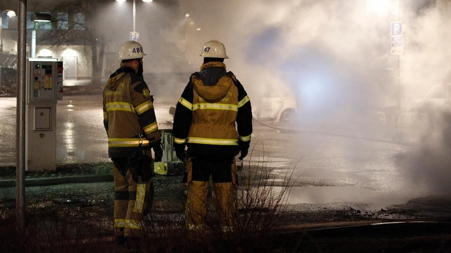 In this picture taken on Monday, Feb. 20, 2017, firefighters survey the scene in the suburb of Rinkeby outside Stockholm. Police in Sweden said Tuesday they were investigating riots that broke out overnight in a predominantly immigrant Stockholm suburb after officers arrested a suspect on drug charges. Spokesman Lars Bystrom said unidentified people, including some wearing masks, threw rocks at police, set cars on fire and looted shops in Rinkeby, north of Stockholm. (Christine Olsson/TT News Agency via AP)