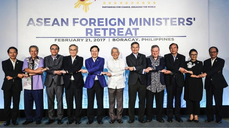 In this photo provided by Presidential Communications Operations Office ASEAN, Foreign ministers from the Association of South East Asian Nations (ASEAN) link arms during the ASEAN Foreign Ministers' Retreat in Boracay, Aklan province, central Philippines, Tuesday, Feb. 21, 2017. From left, Laos' Foreign Minister Saleumxay Kommasith, Malaysia's Foreign Minister AnifH Aman, Myanmar's Minister of State for Foreign Affairs U Kyaw Tin, Thailand's Foreign Minister Don Pramudwinai, Vietnam's Foreign Minister Pham Binh Minh, AMM Retreat Chair and Philippine Secretary of Foreign Affairs Perfecto Yasay, Singapore's Foreign Minister Vivian Balakrishnan, Brunei Darussalam's Minister at the Prime Minister's Office and Second Minister of Foreign Affairs and Trade Pehin Dato' Lim Jock Seng, Cambodia's Senior Minister and Minister for MFAIC Prak Sokhonn, Indonesia's Foreign Minister Retno Marsudi, and ASEAN Secretary-General, ASEAN Secretariat Le Luong Minh. (Presidential Communications Operations Office ASEAN via AP)