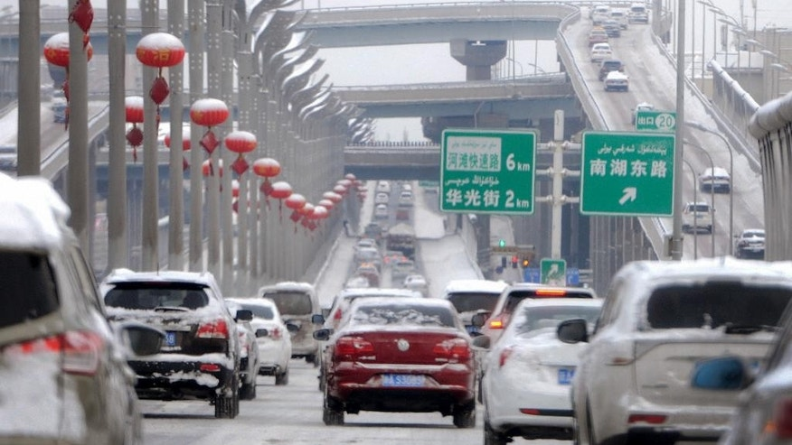 In this Monday, Feb. 20, 2017 photo released by Xinhua News Agency, vehicles run on the snow-covered road in Urumqi, capital of northwest China's Xinjiang Uygur Autonomous Region. A prefecture in China's Xinjiang region is requiring all vehicles to install satellite tracking systems as part of stepped-up measures against violent attacks. Traffic police in Bayingolin Mongol Autonomous Prefecture announced the regulation on Sunday, shortly after thousands of heavily armed police paraded in Urumqi and Communist Party officials vowed to ramp up their campaign against separatists and Islamic militants. (Wang Fei/Xinhua via AP)