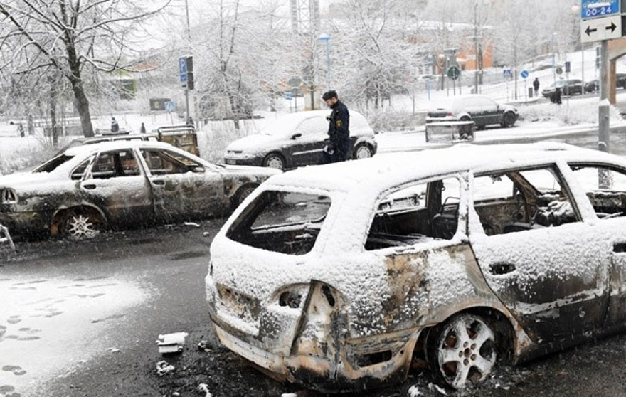 In this picture taken on Monday, Feb. 20, 2017,a policeman investigates a burned out car in the suburb of Rinkeby outside Stockholm. Police in Sweden said Tuesday they were investigating riots that broke out overnight in a predominantly immigrant Stockholm suburb after officers arrested a suspect on drug charges. Spokesman Lars Bystrom said unidentified people, including some wearing masks, threw rocks at police, set cars on fire and looted shops in Rinkeby, north of Stockholm. (Christine Olsson/TT News Agency via AP)