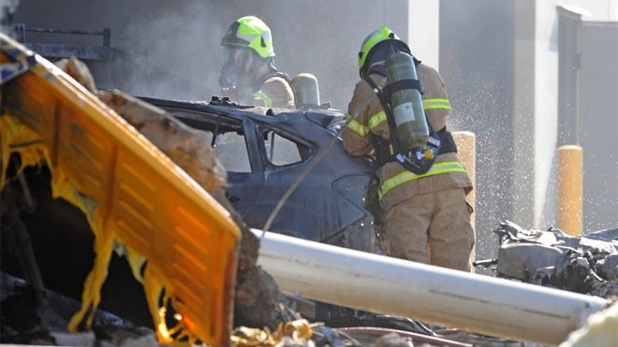 Emergency personnel work at a light plane crashed in Melbourne, Australia