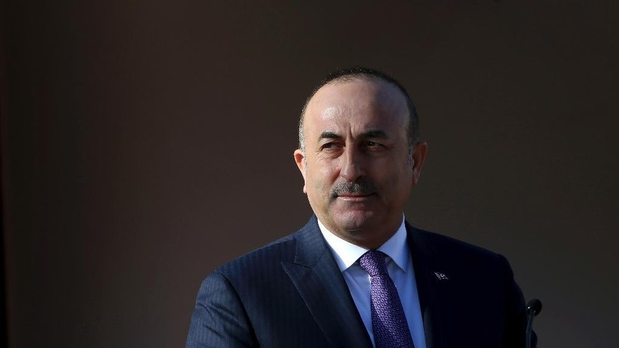 Turkish Foreign Minister Mevlut Cavusoglu speaks to the media during a press conference with Turkish Cypriot leader Mustafa Akinci in Nicosia, Cyprus, Tuesday, Feb. 21, 2017. Cavusoglu says recent Greek Cypriot actions that have fanned insecurity among Turkish Cypriots show that rights for Turkey to militarily intervene on the ethnically divided island are still necessary. (AP Photo/Petros Karadjias)