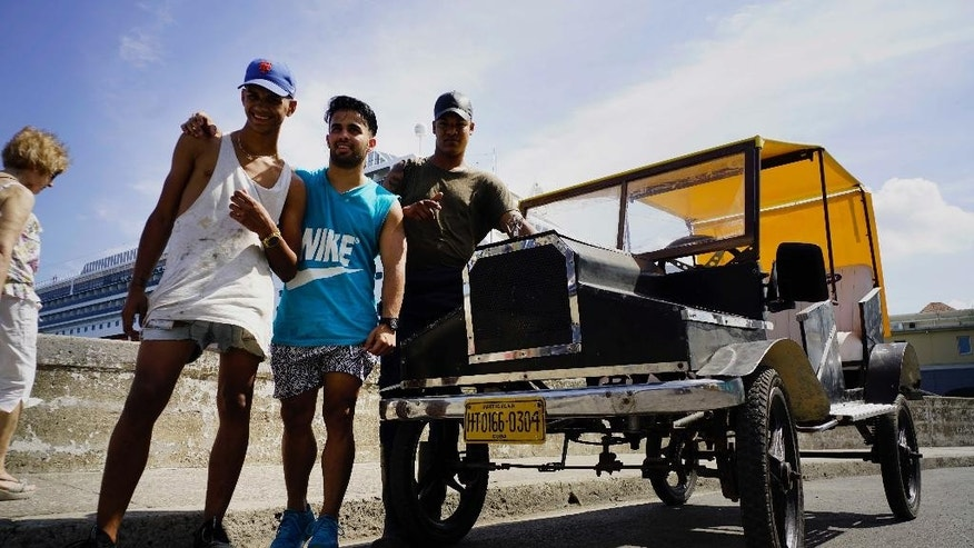 Dany Gomez, center, poses with friends next to his homemade replica of a Model-T Ford, which he pedaled from home to the Malecon sea wall in Havana, Cuba, Monday, Feb. 20, 2017. Gomez says it's not perfect, but allows him and his friends to get around independently, and they can get a little exercise while doing so. (AP Photo/Ramon Espinosa)