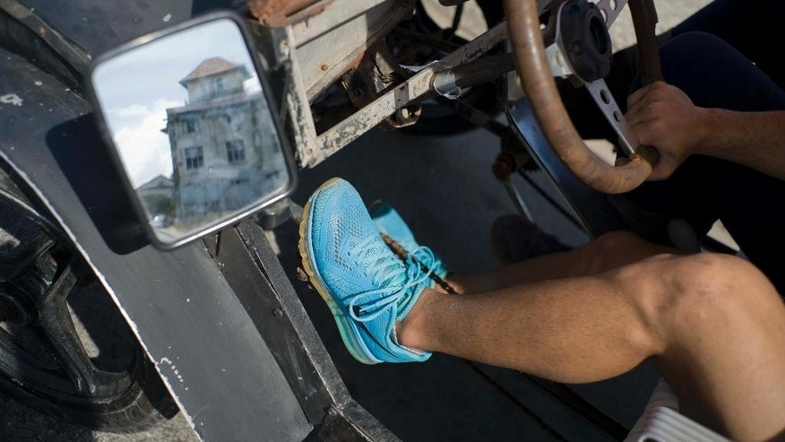 Dany Gomez's feet rest on the pedals of his replica of a Model-T Ford, after traveling in it from home to the Malecon seawall in Havana, Cuba, Monday, Feb. 20, 2017. Transportation can be daunting for many Cubans, with old cars selling for more than $30,000 and new cars more than $50,000. Also, the state-run bus system is overburdened and unreliable. (AP Photo/Ramon Espinosa)