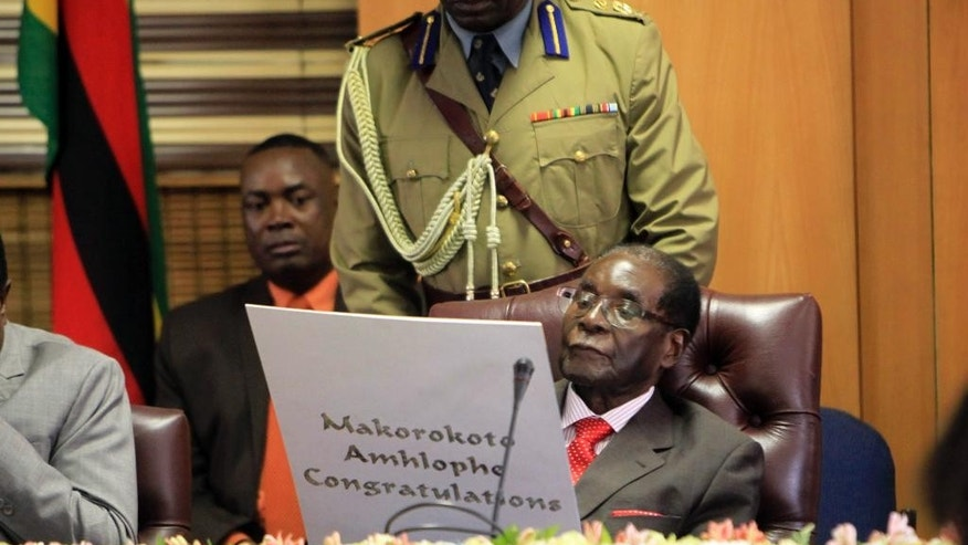 "Zimbabwe's President Robert Mugabe reads his birthday card as he marks his 93rd birthday at his offices in Harare, Tuesday, Feb. 21, 2017. Mugabe described his wife Grace, an increasingly political figure, as ""fireworks"" in an interview marking his 93rd birthday. (AP Photo/Tsvangirayi Mukwazhi)"