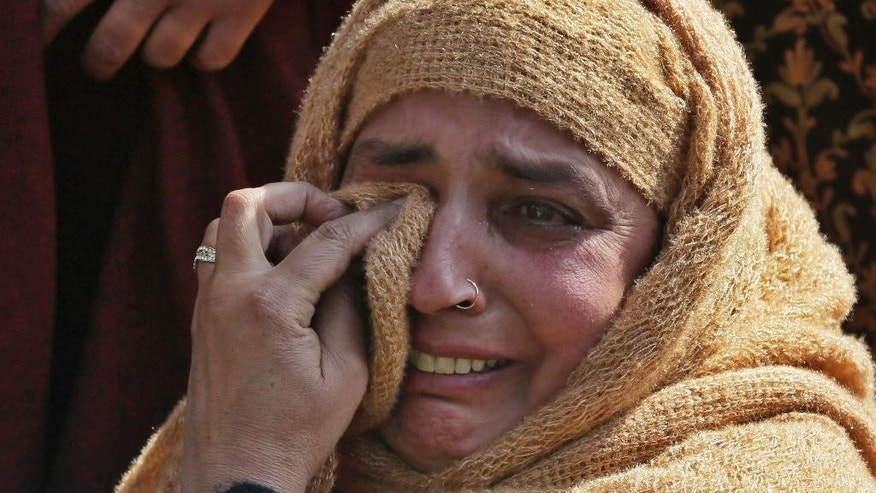 Unidentified relatives of Taja begum, a 60-year-old woman who was killed in shootout grieve at her residence in Moul village, 62 kilometers (39 miles) south of Srinagar, Indian controlled Kashmir, Thursday, Feb.23, 2017. Three Indian soldiers and a woman were killed after rebels ambushed soldiers in the disputed region of Kashmir, police said on Thursday. According to police, the attack triggered a brief exchange of gunfire and a stray bullet hit the 60-year-old woman while she was sleeping in her home. (AP Photo/Mukhtar Khan)
