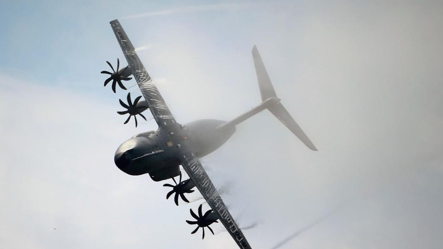 FILE - This Thursday, June 20, 2013, file photo shows an Airbus A400M performing its demonstration flight during the 50th Paris Air Show at Le Bourget airport, north of Paris, France. Surprise new costs for the long-troubled Airbus A400M military jet sent the European planemaker's profits plunging last year despite a rise in commercial aircraft deliveries, Airbus reported Wednesday Feb. 22, 2017. (AP Photo/Francois Mori, File)