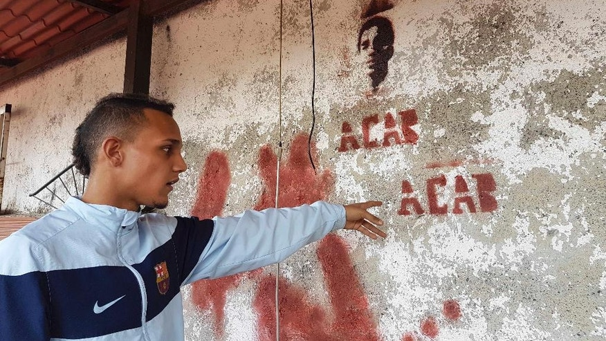 In this Nov. 10, 2016 photo, Jhorman Valero points to the image of his late cousin Bassil da Costa, which he stenciled on the terrace wall of his home in Guatire, Venezuela. Valero took his 24-year-old cousin, Bassil da Costa, to join a nationwide protest against the administration of President Nicolas Maduro three years ago. Hours later, Bassil was bleeding in his arms, the first of a rash of young people to be killed by security forces. (AP Photo/Ricardo Nunes)