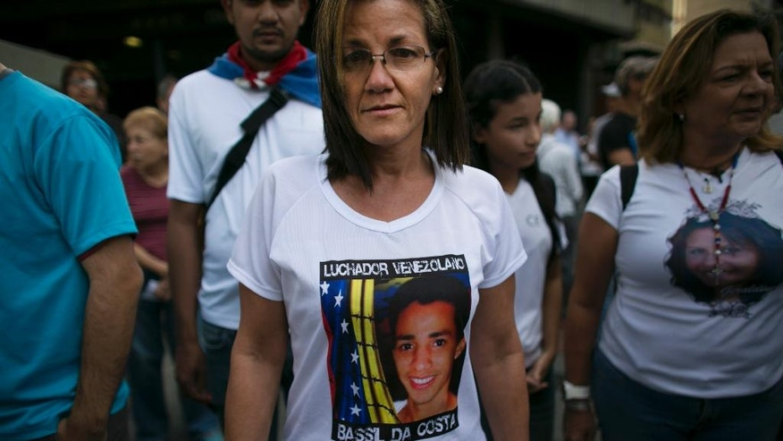 "In this Feb. 12, 2017 photo, Jineth Frias poses for a photo in a T-shirt featuring her slain son, Bassil da Costa, at an anti-government protest marking the third anniversary of his killing by security forces during weeks of unrest in Caracas, Venezuela. In the three years since his death, her family's predicament, like that of Venezuela, has only worsened. Her refrigerator is almost always empty and as a result she's lost 10 kilograms (22 pounds), in what Venezuelans call the ""Maduro Diet."" ""I know it sounds terrible,"" she confides between tears, ""but I thank God he's not here to see this."" (AP Photo/Ariana Cubillos)"