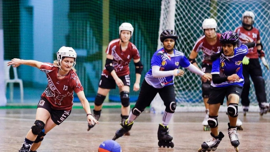 In this Tuesday, Feb. 21, 2017 photo, Aija Apsipe, left, of Latvia follows the ball during the 4th Roll Ball World Cup quarterfinal match against India at Shaheed Sohrawardi Indoor Stadium in Dhaka, Bangladesh. Bangladesh hosted the championship for an unusual sport, roll ball, where players on roller skates dribble and pass a basketball-sized ball that they try to throw into a small soccer-type goal. About 750 players from 40 countries around the world took part. Top honors, both for men and women, went to India, where the sport was invented. (AP Photo/A.M. Ahad)