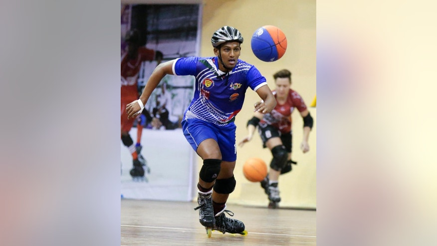 In this Tuesday, Feb. 21, 2017 photo, Chandran Sharma of India skates to the ball during the 4th Roll Ball World Cup quarterfinal match against Zambia at Shaheed Sohrawardi Indoor Stadium in Dhaka, Bangladesh. Bangladesh hosted the championship for an unusual sport, roll ball, where players on roller skates dribble and pass a basketball-sized ball that they try to throw into a small soccer-type goal. About 750 players from 40 countries around the world took part. Top honors, both for men and women, went to India, where the sport was invented. (AP Photo/A.M. Ahad)