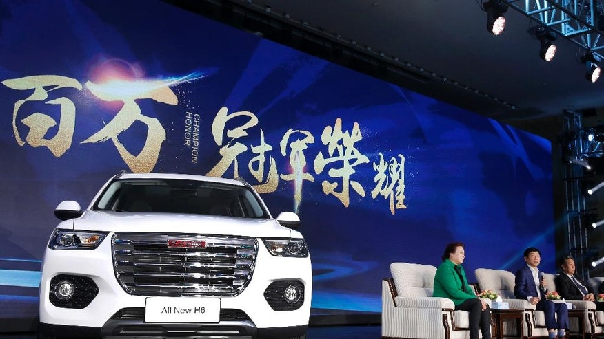 In this Sunday, Feb. 19, 2017 photo, Wei Jianjun, chairman of Great Wall Motors Ltd., second from right, speaks as a newly unveiled Haval SUV H6 model is displayed during a reception celebrating it sales passing the one million mark, at Great Wall headquarters in Baoding in north China's Hebei province. Great Wall Motors became China's most profitable automaker by making almost nothing but low-priced SUVs. Now it wants to expand into global markets. (AP Photo/Andy Wong)