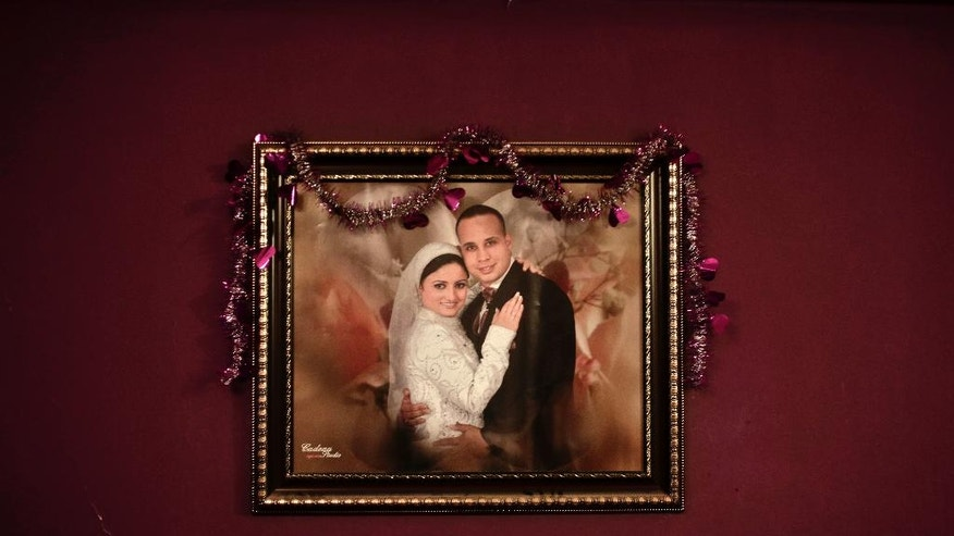 In this Sunday, Feb. 12, 2017 photo, a wedding portrait of Ahmed Maher, a leader of the April 6 youth movement group that had a leading role in the 2011 uprising against former President Hosni Mubarak, and his wife Riham hangs on a wall at their home, in Cairo, Egypt. Maher's nightly detention may be the harshest interpretation possible of regulations on police observation, which often involves showing up at a police station each day, signing a log and leaving, according to rights lawyers familiar with such cases. But in Maher's case, he is being forced to stay in the station every night from 6:15 p.m. until 6:15 a.m. (AP Photo/Nariman El-Mofty)