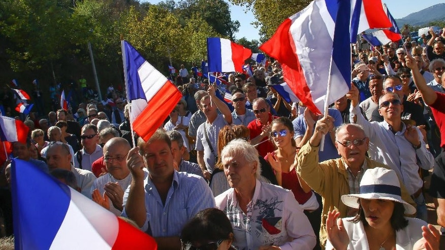 FILE - In this Saturday, Oct. 8, 2016 file photo, supporters of far right National Front party attend a rally in Pierrefeu, southeastern France. If Marine Le Pen has her way, the French will soon pay for their baguettes with francs, not euros. The presidential candidate from the anti-EU, anti-immigration National Front party is all about national sovereignty and independence. She wants France to take control of its money, subject to a referendum that would lead France out of the European Union and its shared currency. (AP Photo/Philippe Farjon, file)