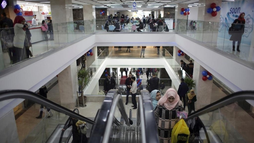 In this Saturday Feb. 18, 2017 photo, Palestinians shop in the first indoor shopping mall in the Gaza Strip, in Gaza City. In a welcome sign of normalcy, the first indoor shopping mall -- complete with an international retail chain, three-story bookstore and food court -- has opened in the Gaza Strip. The owners have overcome conflict and an Israeli-Egyptian blockade to build the gleaming 1,800 sq. meter (19,000 sq. feet) shopping center. (AP Photo/ Khalil Hamra)