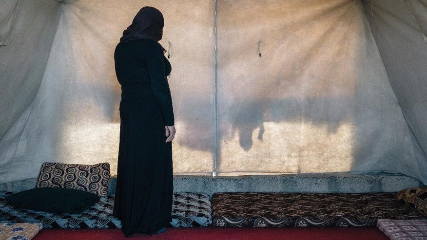 In this Jan. 12, 2017 photo, 39-year-old Gorwe stands inside the tent she shares with family members at the Sharya camp for civilians displaced by war in Iraq. She escaped Islamic State militant captivity and has two sisters-in-law who are now living in Germany and receiving treatment in German trauma specialist Jan Kizilhan's program. (AP Photo/Alice Martins)