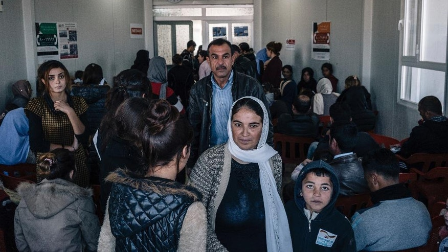 In this Jan. 12, 2017 photo, Yazidis fill a crowded waiting room at a clinic inside the Sharya camp for civilians displaced by war in Iraq. A new psychological trauma institute is being established at the university of Dohuk in Iraq, the first in the entire region. The program will train local mental health professionals to treat Islamic State victims, including thousands of Yazidi women and children. It will open at the end of the month. (AP Photo/Alice Martins)