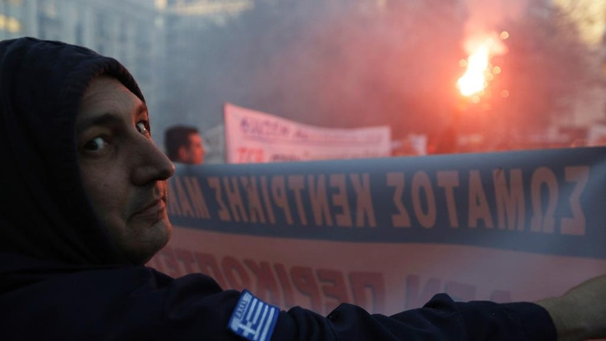 A Greek coastguard officer holds a banner in front of a flare as he gathers with firefighters and police officers, during an anti-austerity protest in Athens, Wednesday, Feb. 22, 2017. Unionists are protesting funding, pay and hiring cuts implemented over the past seven years of Greece's bailout-linked austerity program, as well as what they describe as severe shortages in service equipment, including police patrol cars. (AP Photo/Thanassis Stavrakis)