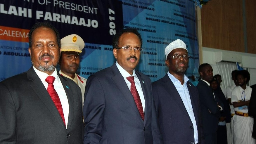 "Somalia's President Mohamed Abdullahi Mohamed, also known as Farmajo, center, is accompanied by two former presidents Hassan Sheikh Mohamud, left, and Sharif Sheikh Ahmed, right, at his inauguration ceremony in Mogadishu, Somalia Wednesday, Feb. 22, 2017. Somalia's new leader, who also holds U.S. citizenship, was inaugurated Wednesday while promising to restore dignity to the troubled Horn of Africa nation but warning it will take another two decades to ""fix"" the country. (AP Photo/Farah Abdi Warsameh)"