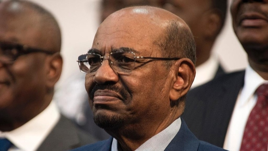 FILE - In this June 14, 2015 file photo, Sudanese President Omar al-Bashir smiles during a visit to Johannesburg, South Africa. A South African court ruled Wednesday, Feb. 22, 2017 that the government's decision to withdraw from the International Criminal Court without parliament's approval was unconstitutional. South Africa's withdrawal announcement last year followed a 2015 dispute over a visit by Sudanese President Omar al-Bashir, who is wanted by the ICC for alleged war crimes, crimes against humanity and genocide in Darfur. (AP Photo/Shiraaz Mohamed, File)