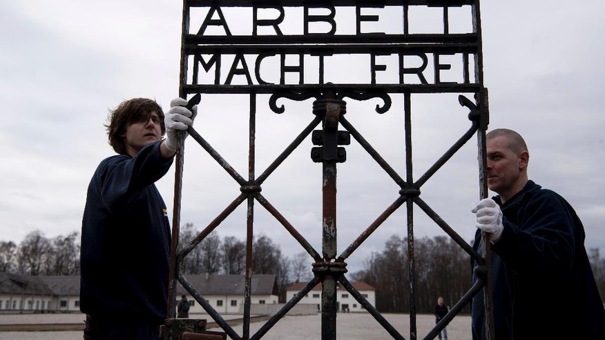 "Employees of a transport company carry the gate with the writing ""Arbeit macht frei"" (Work Sets you Free) at the memorial of the former  Nazi concentration camp in Dachau, Germany, Wednesday, Feb. 22, 2017.  The gate  was stolen in 2014 and reappeared in November 2016 near the city of Bergen in Norway.  (Sven Hoppe/dpa via AP)"